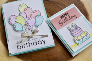 This image features two diy best friend birthday cards atop a wooden stump. Both of these diy birthday cards for best friend are white paper layered atop a blue card backing. These birthday cards for friends handmade are both colored lightly with colored pencil in a pastel color scheme. The lefthand of the handmade birthday cards for friends depicts a large bunch of balloons and a small bow. The sentiment on this lefthand of the handmade friend birthday cards reads best wishes on your birthday. The righthand of the two diy birthday cards for friends is decorated with a cake and the sentiment reads Happy birthday.