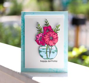 This image shows a diy flower birthday card featuring a stamped anddie cut bouquet of flowers in a bowl. This diy birthday card for friend is white with a blue outline, and the sentiment reads simply happy birthday.