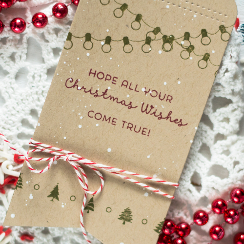 Svitlana's Christmas in July Craft is shown. It's a diy gift tag decorated with trees and strings of lights and the sentiment on it reads Hope all your Christmas wishes come true.