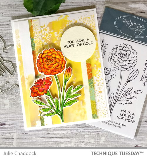 The card in this image is one of the more visually busy marigold flower card making ideas. The background of this card features a mixing and splattering of colors and strips layered on top of each other, the stamped and die cut marigold itself is colored in with contrasting deep red and lighter orange. The sentiment featured reads You have a heart of gold.